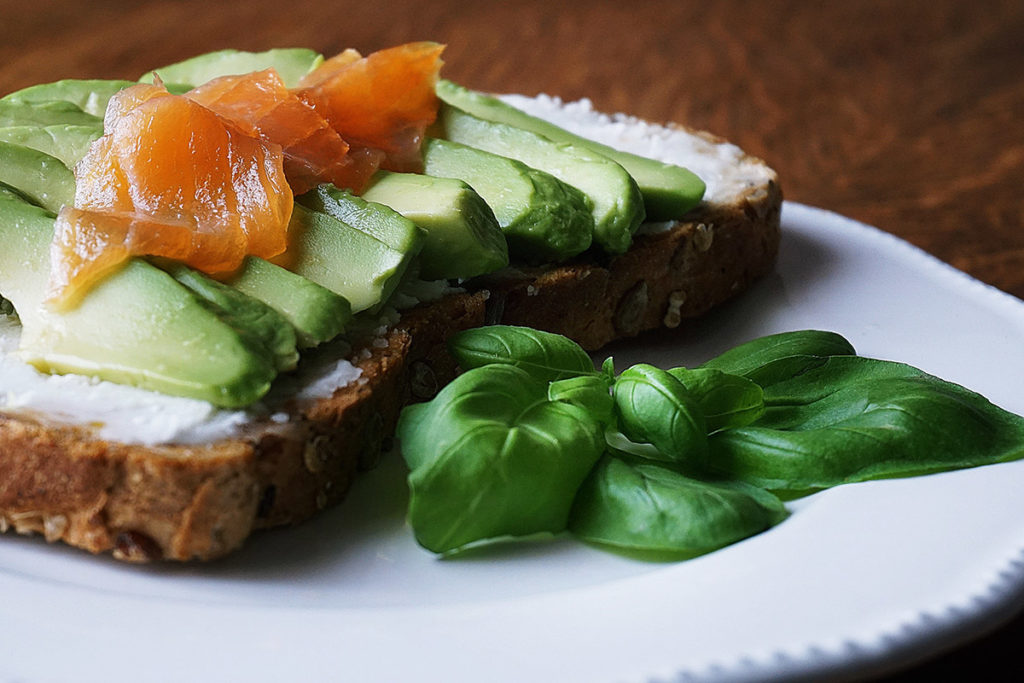bread with sliced avocado and salmon